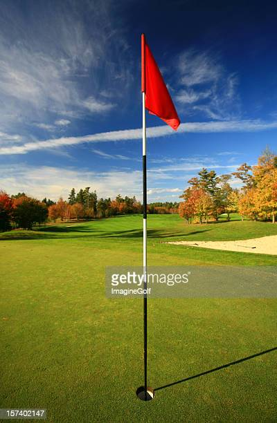 red flag on a beautiful golf course in fall - golf flag stock photos and pictures
