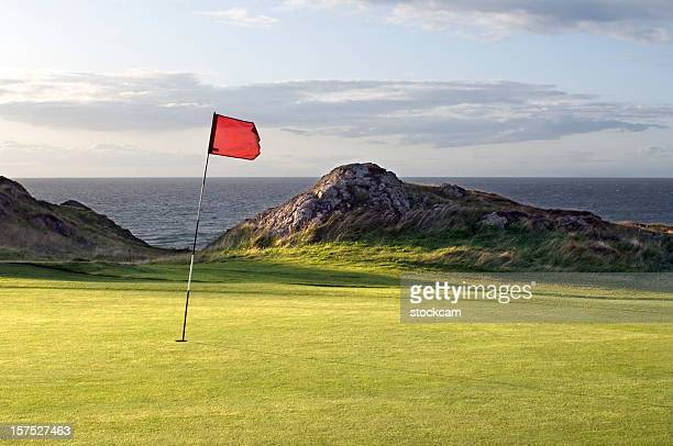 red flag on hole of golf course green - golfbaan green stockfoto's en -beelden