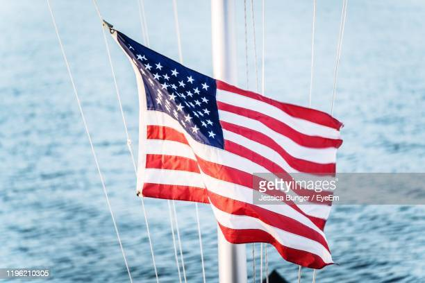 red flag on mast over sea - american flag ocean stock pictures, royalty-free photos & images