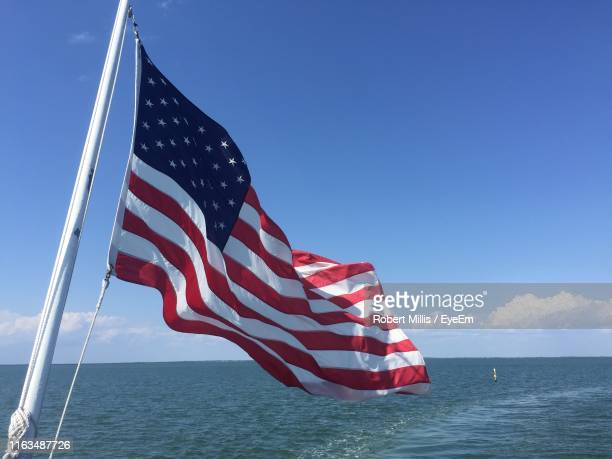 red flag on sea against blue sky - american flag ocean stock pictures, royalty-free photos & images