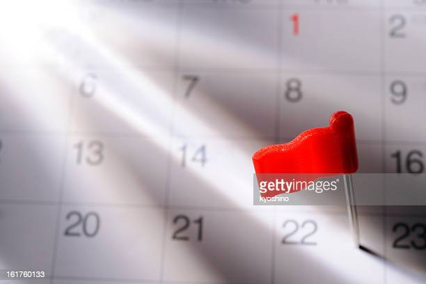 Red flag pushpin in calendar with light rays