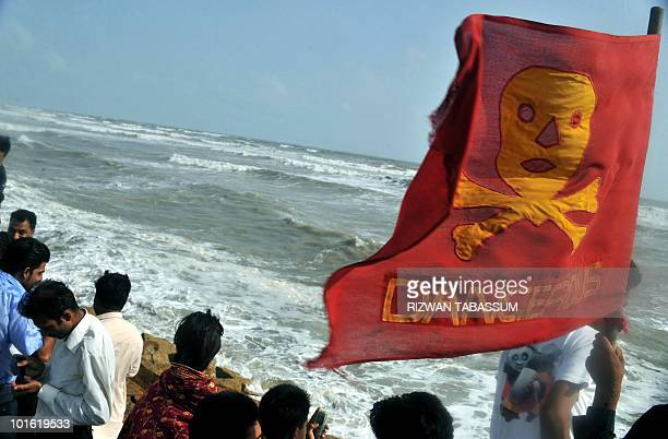 A red flag saying 'dangerous' adorned with skull and bones flies in the sea breeze as Pakistani onlookers and revellers throng the popular Seavies...