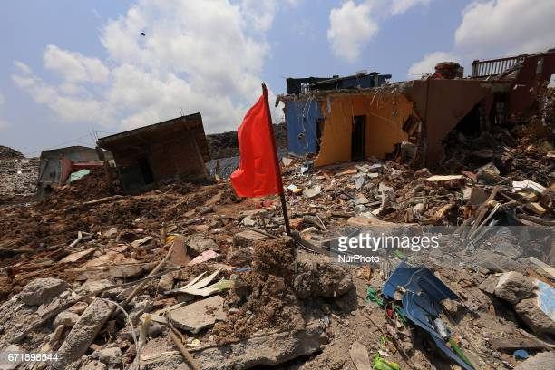 A Red flag that demarcate danger zones is seen among the debris of damaged houses days after the collapse of a garbage mound in Meetotamulla on the...