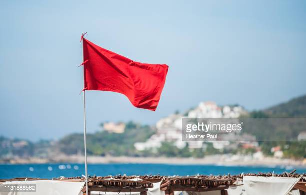 red flag warning at beach resort - flag stock pictures, royalty-free photos & images