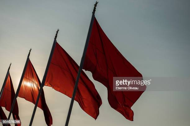 Red flags are raised on Tiananmen Square before the seventh plenary session of the 13th National People's Congress at the Great Hall of the People on...