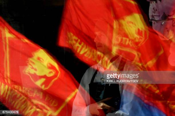 Red flags with the portrait of late Soviet leader Vladimir Lenin are reflected in the window of a shop during a Russian Communist party May Day...