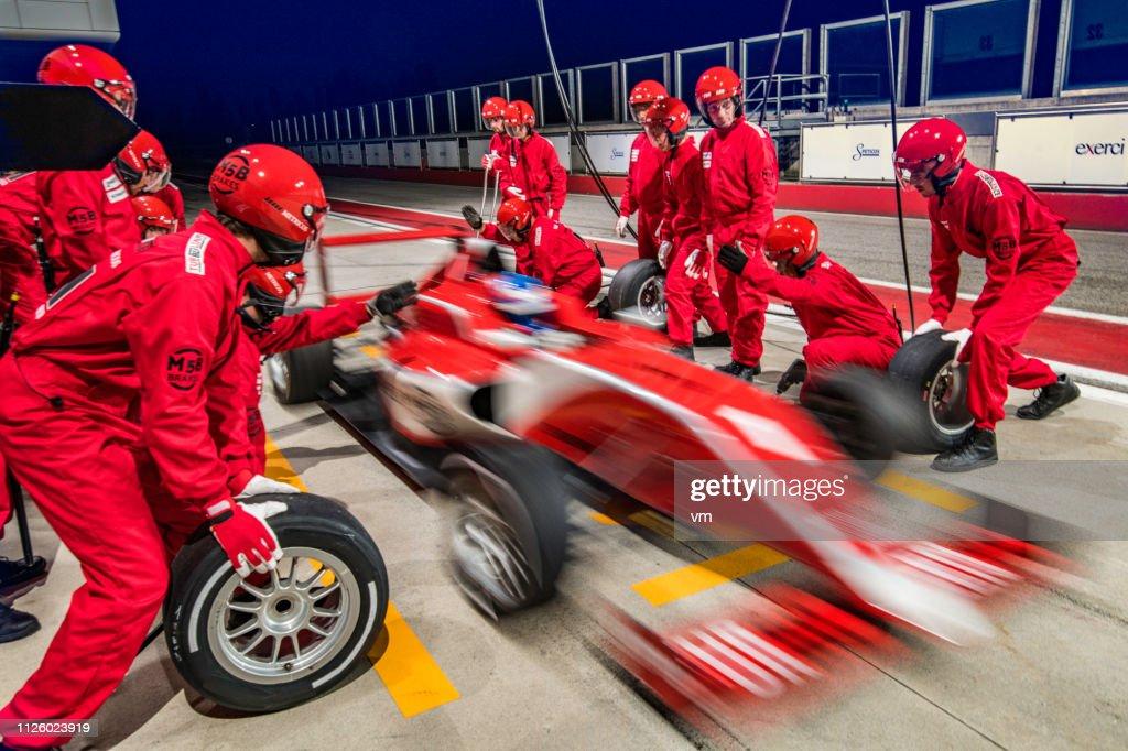 Red formula race car leaving the pit stop : Foto de stock