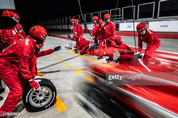 red formula race car leaving the pit stop - sports race stock pictures, royalty-free photos & images