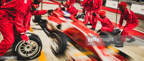 red formula race car leaving the pit stop - grand prix motor racing stock pictures, royalty-free photos & images