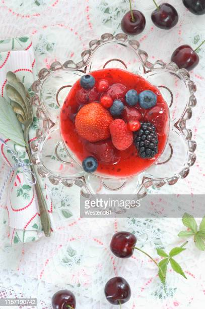 red fruit jelly with whole fruits in glass bowl - doily stock photos and pictures