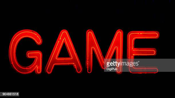 "Red ""GAME"" neon sign on black background in the night"