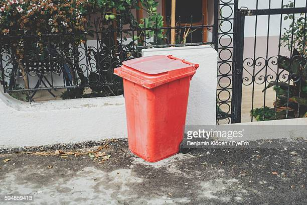 Red Garbage Can Against Fence Of House
