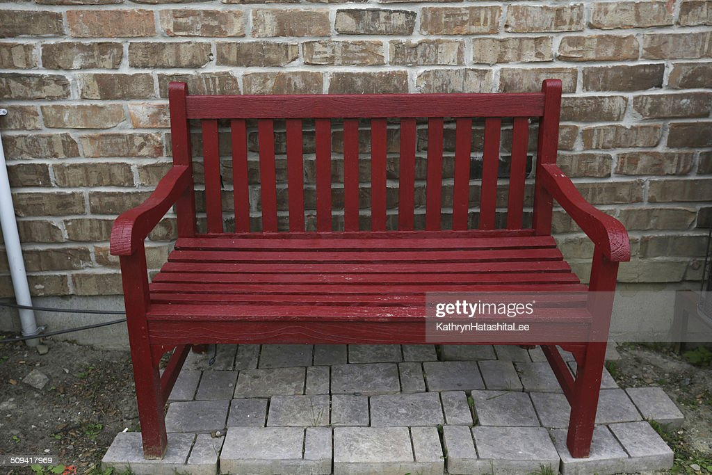 Red Garden Bench And Brick Wall In Toronto, Ontario, Canada : Stock Photo