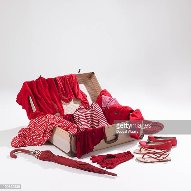 Red garments spilling out of white suitcase.
