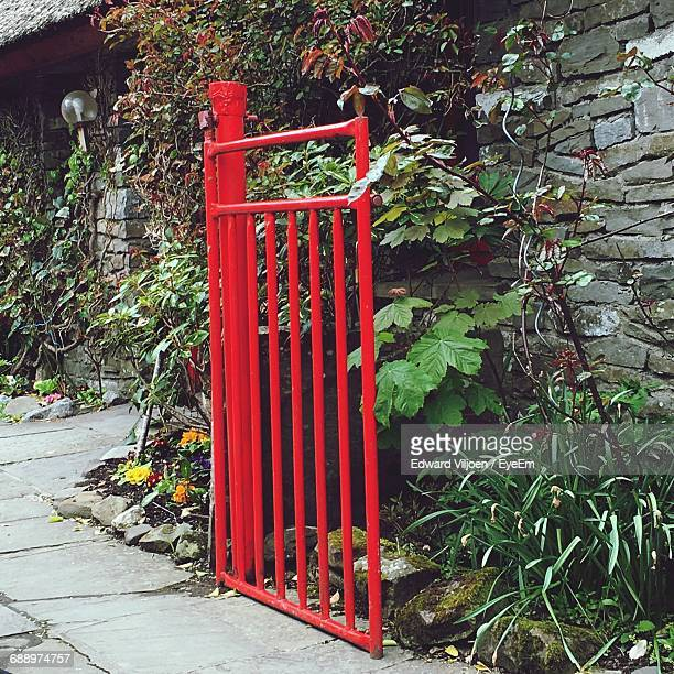 Red Gate Against Plants Outside House