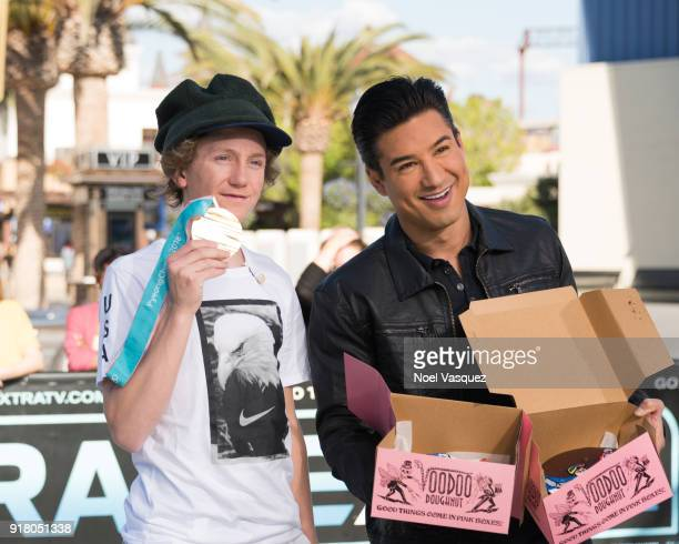 Red Gerard holds up his gold medal and Mario Lopez displays donuts with Olympic gold medal icing at 'Extra' at Universal Studios Hollywood on...