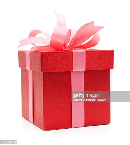 red gift against white background - gift stock pictures, royalty-free photos & images