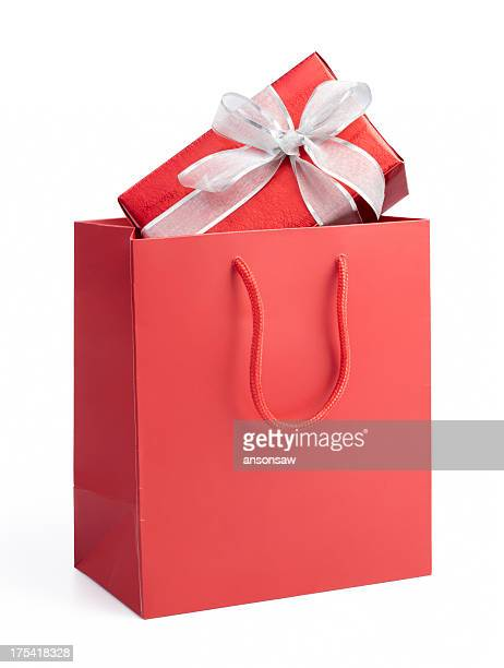 Red gift box with white bow ribbon in a red gift bag