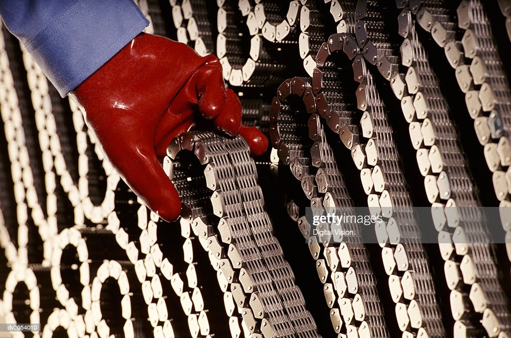 Red Gloved Hand Removing a Coiled Chain : Stock Photo