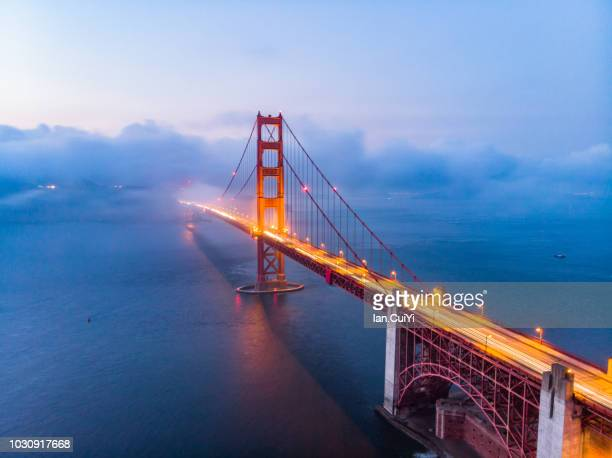 red golden gate bridge under a foggy sky (dusk) - san francisco fotografías e imágenes de stock
