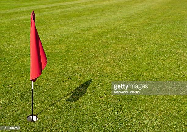 Red golf flag against green grass