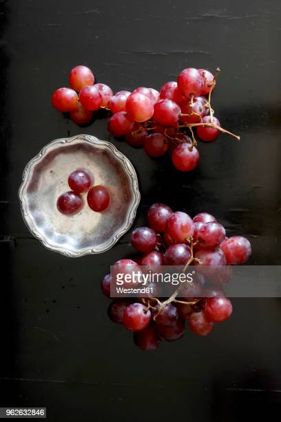 red grapes and metal plate on dark ground - red grape stock photos and pictures