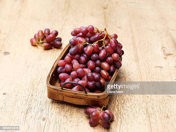 red grapes in vintage wicker basket - red grape stock photos and pictures