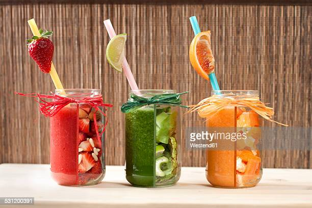 Red, green and orange vegetable and fruit smoothies