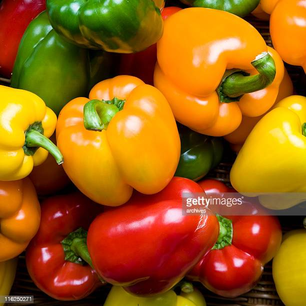 Red green yellow and orange peppers as a background