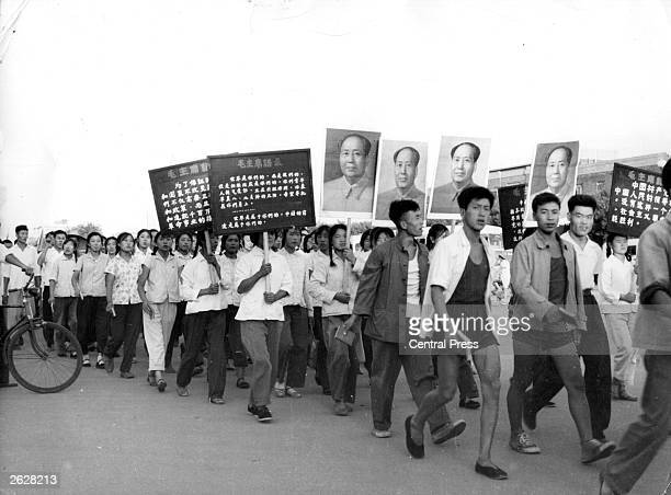 Red Guards carry portraits of their Communist leader Mao as they parade through Peking to the Soviet Embassy in protest at 'Soviet Revisionism'
