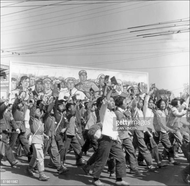 Red Guards high school and university students waving copies of Chairman Mao Zedong's 'Little Red Book' parade in June 1966 in Beijing's streets at...