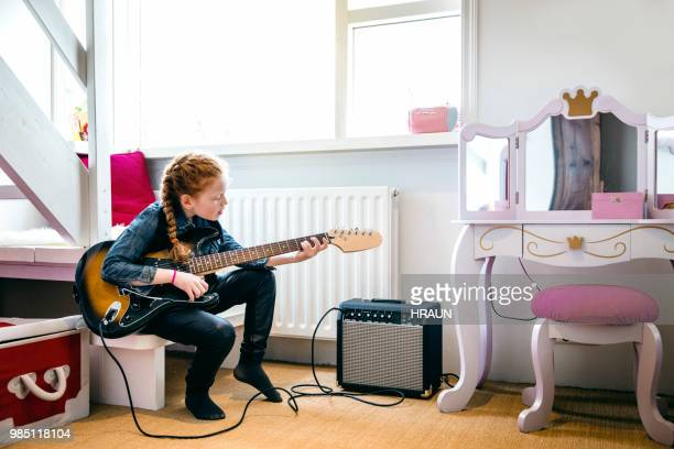 red hair girl playing electric guitar in her bedroom. - electric guitar stock pictures, royalty-free photos & images