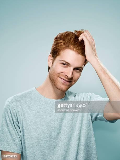 Red hair male smiling, hand running through hair