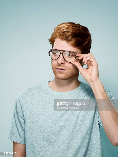 Red hair male with glasses, hand holding glasses