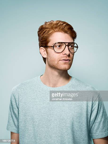 Red hair male with glasses looking away