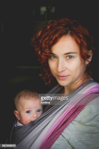 red hair mother holding baby daughter on black background - black ginger baby stock photos and pictures