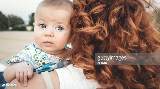 Red hair mother holding her baby daughter on the beach