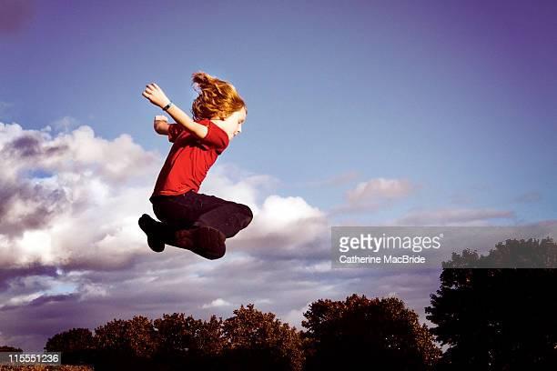 red haired boy jumping - catherine macbride stock-fotos und bilder