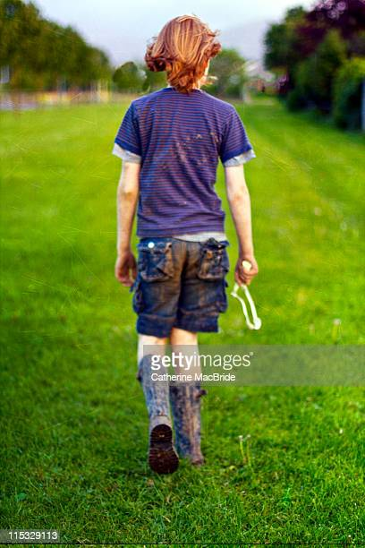 red haired boy walking away - catherine macbride stock pictures, royalty-free photos & images