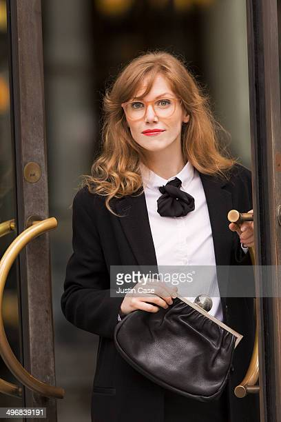 red haired business woman opening a glass door