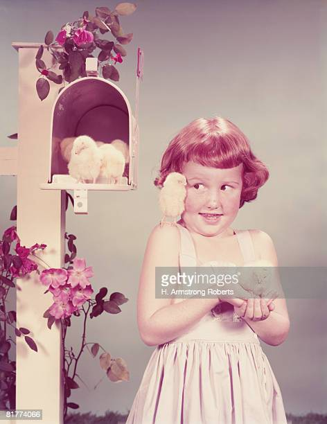 red haired girl by mail box holding chick, another on her shoulder and more in mailbox. (photo by h. armstrong roberts/retrofile/getty images) - domestic mailbox stock pictures, royalty-free photos & images