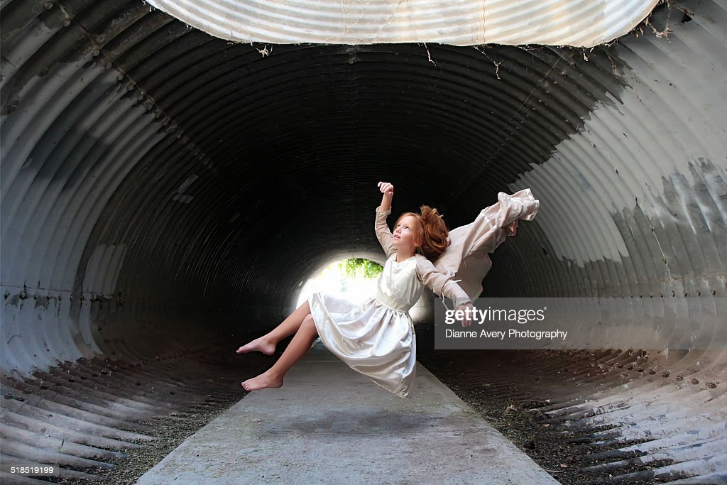 Red haired girl floating in tunnel : ストックフォト
