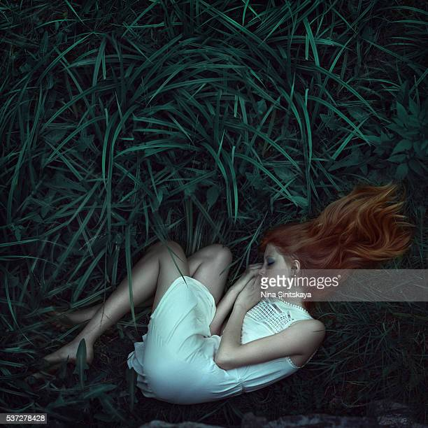 Red haired girl in a short white dress laying on the green grass