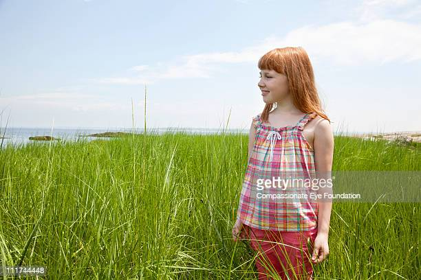"""red haired girl standing in tall grass - """"compassionate eye"""" stock pictures, royalty-free photos & images"""