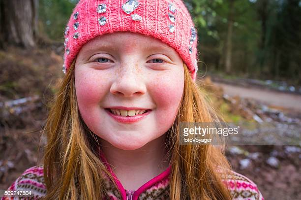 Red haired girl wearing woolly hat smiling on forest trail