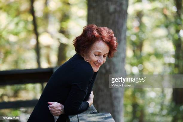 Red haired senior woman smiles and looks out over porch