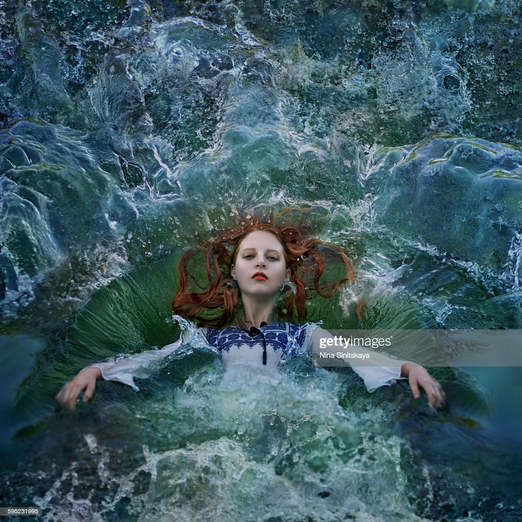 Red haired woman falling into water : Stock Photo