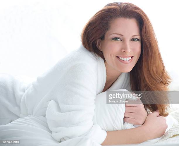red haired woman head shot in robe. - older redhead stock pictures, royalty-free photos & images