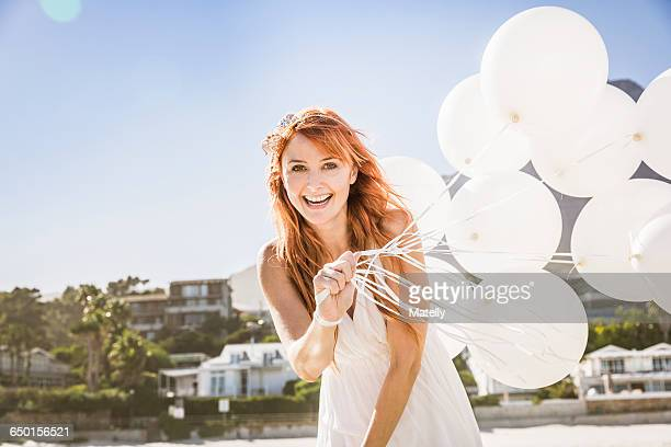 Red haired woman holding balloons looking at camera smiling