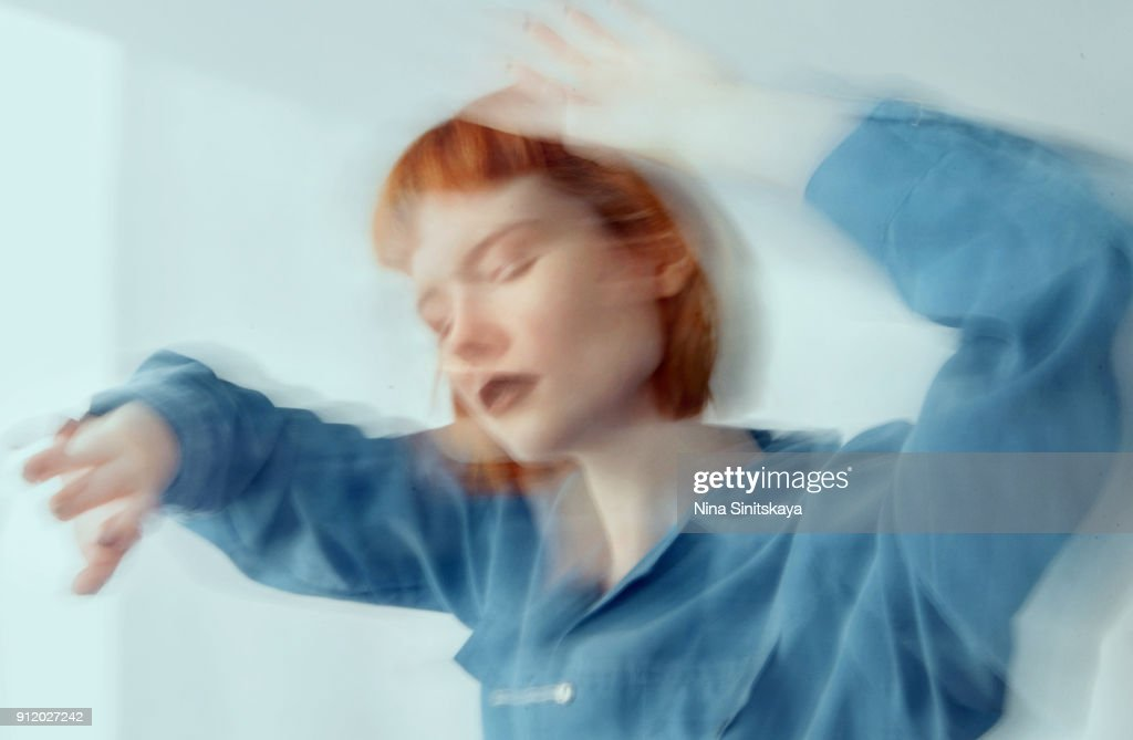 Red haired woman in blue shirt dancing, blurred motion - long exposure : Stock Photo